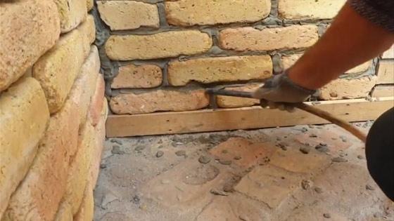 A fuga száradása után egy bottal, csővel kikaparjuk a felesleges fugát, hogy sima legyen a rések közötti felület
